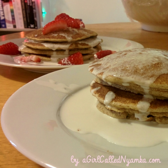 Pancakes topped with strawberries and coconut cream